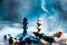 Two Chess Figure Kings Of Different Colors Standing  In Smoke While All The Other Figures Are Down