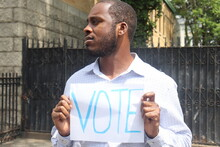 African American Man Holding White Paper Sign With The Word Vote Written In Blue Letters