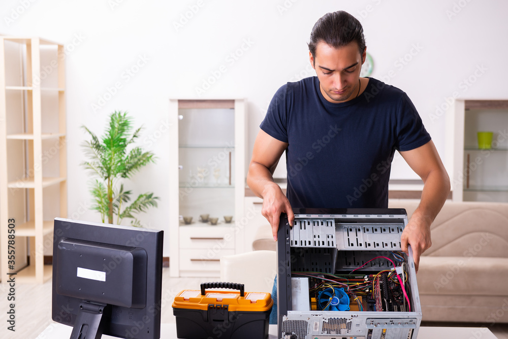 Young man repairing computer at home