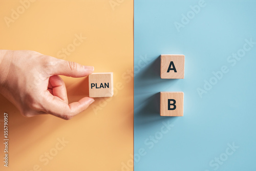 Photo Hand choose wooden cube with the word PLAN A to PLAN B on blue and yellow background