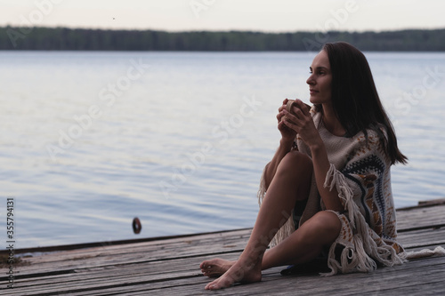 Fotografia, Obraz A beautiful dark-haired woman sits on an old wooden pier in the early hours of d