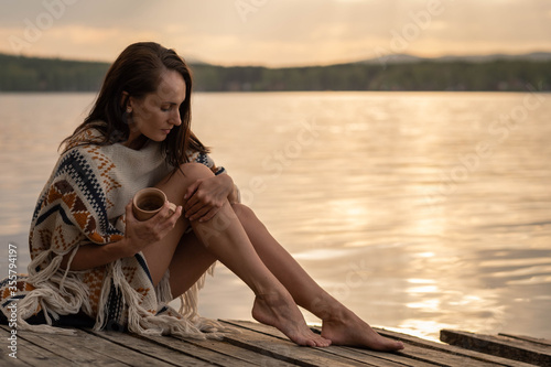 Obraz na plátne A beautiful dark-haired woman sits on an old wooden pier in the early hours of d
