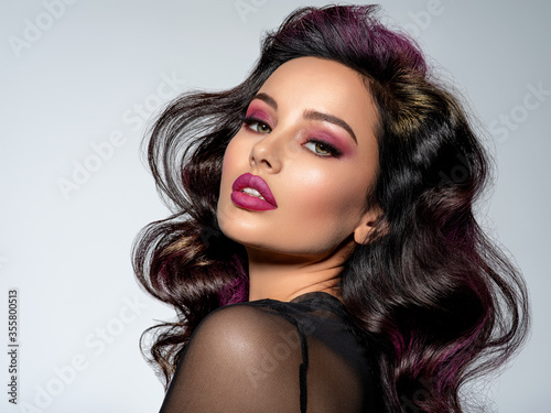 Obraz Portrait of beautiful young woman with bright maroon makeup. Beautiful brunette with bright cherry lipstick on her lips. Pretty girl with long black hair. Brunette with brightly colored hair. - fototapety do salonu