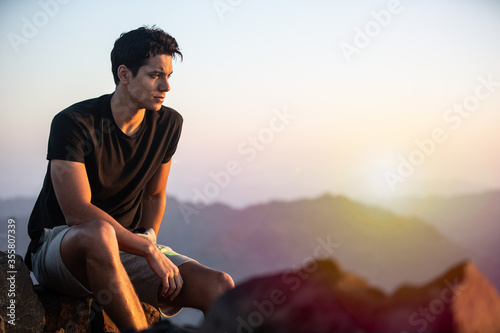 Photo Thoughtful young man sitting on a rock atop of a mountain peak looking at the landscape view during a beautiful sunset