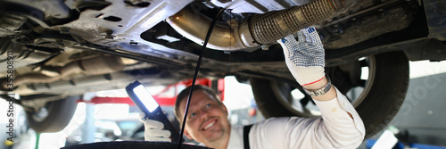 Mechanic conducts thorough inspection car garage. Male mechanic in working overall stands under car and shines lantern on car parts in search malfunction. Technician smiles while draining old oil.