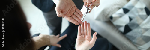 Male businessman hand passes the key to a woman from new housing Canvas Print
