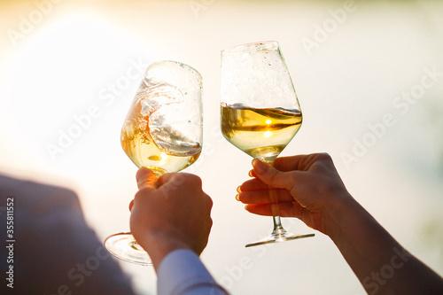 Obraz na płótnie glasses with white wine splash in the hands