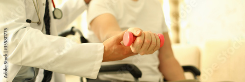 Handicapped man sits working out dumbbell arm Canvas Print