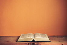 Open Holy Bible On A Old Wooden Table. Beautiful Orange Wall Background..