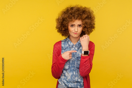 Portrait of upset impatient woman with curly hair showing wrist watch and looking disappointed at camera, reminding of late time, asking to hurry Tapéta, Fotótapéta