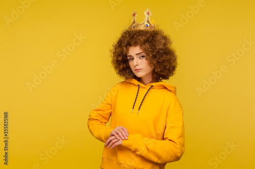 Photo I am queen! Selfish haughty curly-haired woman wearing crown on head and looking with arrogance supercilious, being egoistic with over-inflated ego