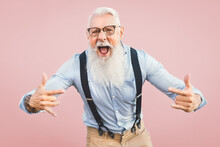 Senior Man Having Fun Posing In Front Camera - Happy Mature Male Enjoying Retired Time - Elderly People Lifestyle And Hipster Culture Concept - Pink Background