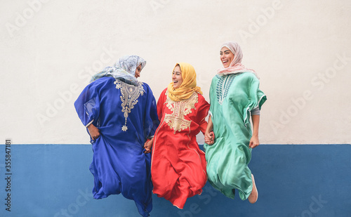 Obraz na plátně Happy Muslim women having fun jumping and laughing together outdoor - People lif
