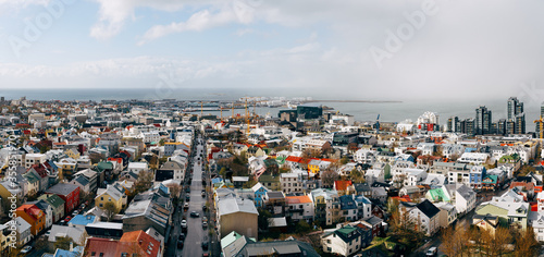 Fotografie, Obraz Beautiful wide-angle aerial view of Reykjavik, Iceland with harbor and skyline mountains and scenery beyond the city, seen from the observation tower of Hallgrimskirkja Cathedral