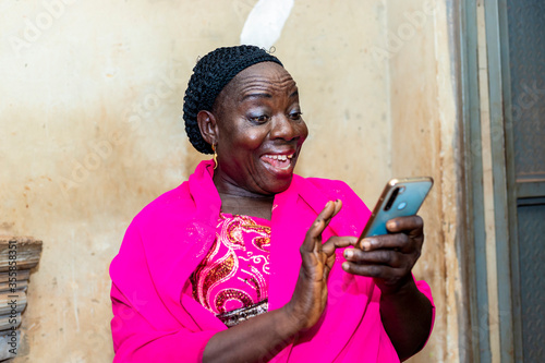 Obraz cheerful excited old black african woman receiving some good news with her smart phone.happy senior lady using mobile phone - fototapety do salonu