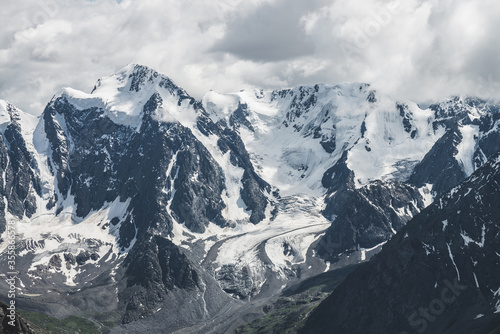 Fototapeta Atmospheric alpine landscape with massive hanging glacier on giant mountain