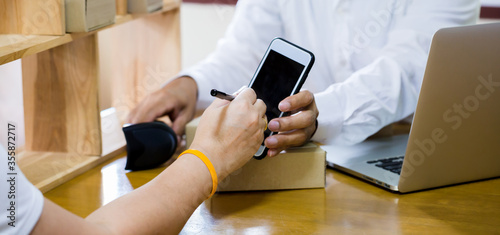 Photo Customer appending signature on smartphone with staff in post office and connect to laptop