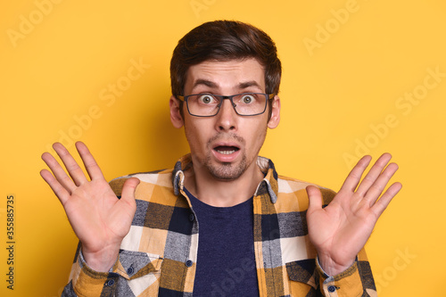 Photo Young amazed handsome man in glasses standing on yellow wall raising arms wondering, astonished to see something, facial expression, shocked with news, amazed