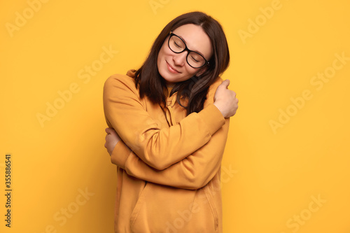 Fotografie, Obraz Closeup portrait confident smiling woman in glasses and orange cozy jumper holding and hugging herself isolated on yellow background