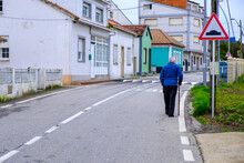 ILLA DE AROUSA, SPAIN - MARCH 4, 2018: An Old Man Walks By Helping Himself With A Cane, Along The Edge Of The Main Road That Crosses The Village.