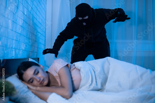 Fotomural Thief ready to attack woman who is sleeping in bed
