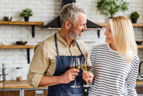 Fotografía Happy senior couple drinking wine at kitchen while cooking