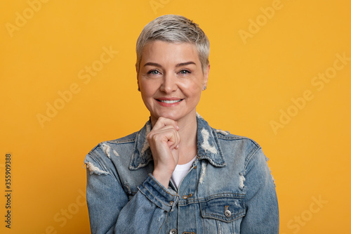Obraz na plátně Beautiful Mature Woman In Denim Jacket Touching Chin And Looking At Camera