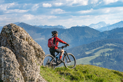 Fotografia pretty senior woman riding her electric mountain bike in warm dawn sunlight and