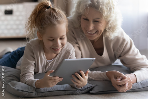 Obraz Playful happy elderly grandmother and little granddaughter relax lying on floor at home watching video pad gadget, smiling mature grandparent have fun play using modern tablet with small grandchild - fototapety do salonu