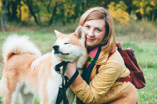 Girl Plays With Husky White Ginger Dog In Park In Fresh Air. Feeling Portrait Of Woman And Cute Foxy Dog Close-up. Beautiful Red Husky Dog Playing With Girl In Autumn Colors. Walking Pet With Owner.