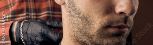 Obraz Barber cuts a guy at the hairdresser. Short haircut and alignment of hair contours. Close up portrait of a customer. Hair care. - fototapety do salonu
