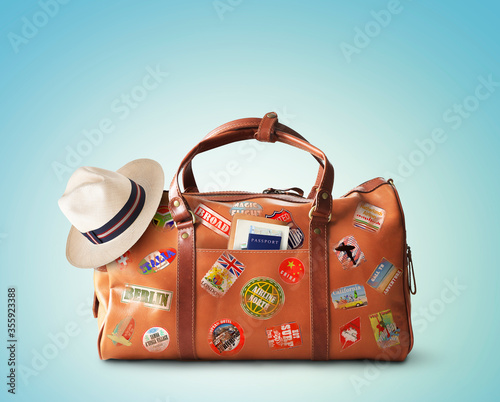 Fototapeta Vacation concept, large classic brown leather travel bag with hat obraz