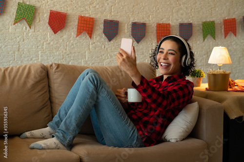 Fototapeta Cheerful Young adult black brazilian woman with headphone looking at cell phone screen Indoors at home living room. Holidays, leisure, enjoyment, music, sound, concept. obraz