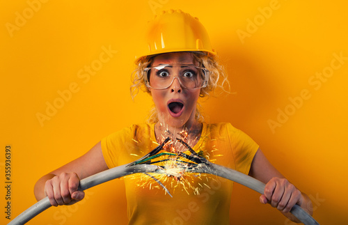 Worker girl with hat breaks an electric cable. Yellow background Canvas Print