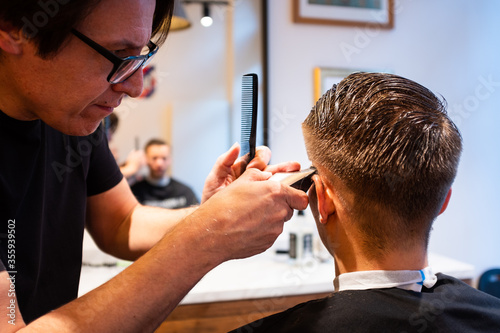Barber trims the hair of young man with a razor