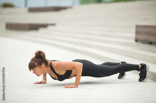 Fototapeta beautiful young woman with a sports figure is engaged in training outdoors