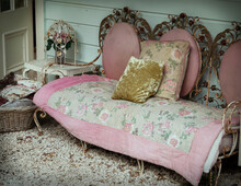 A Vintage Wrought Iron Sofa With Shabby Chic Cushions And Throw