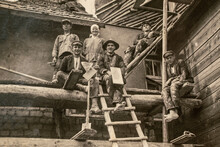 Latvia - CIRCA 1920s: Photo Of Builders Working On Site. Sitting On Scaffolding. Archive Vintage Black And White Photography
