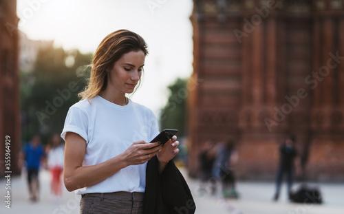 Valokuvatapetti Portrait of beautiful traveler woman reading message on smart phone walking arc
