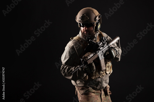 Obraz na plátně American special forces against a dark background, a soldier in military equipme