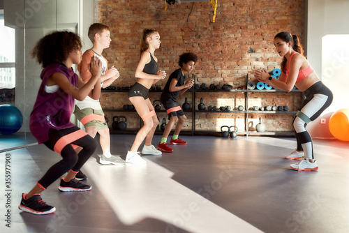 Obraz na plátně Full length shot of kids working out using resistance band in gym together with female trainer
