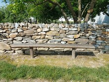 Wood Bench, Stone Wall, And Sign That Says Picnic Area