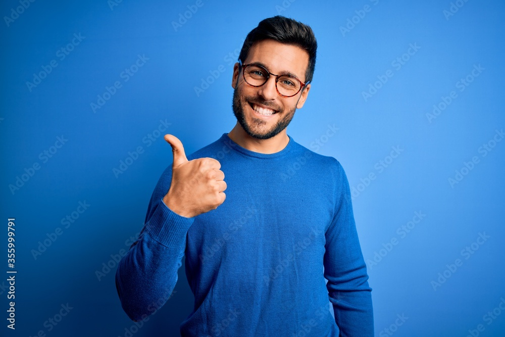 Fototapeta Young handsome man with beard wearing casual sweater and glasses over blue background doing happy thumbs up gesture with hand. Approving expression looking at the camera showing success.
