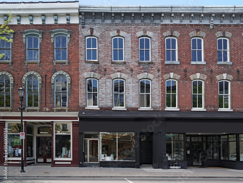 facade of old brick buildings with stores at street level and apartments above