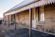 Historic Australian Sandstone Brick Cottage Exterior With Verandah Patio, Corrugated Iron Roof