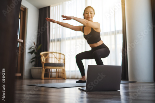 Fotomural A beautiful young asian woman doing squats while watching online workout tutoria