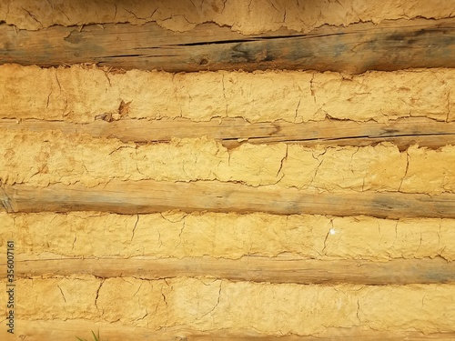 orange dried mud or adobe wall with wood Canvas Print