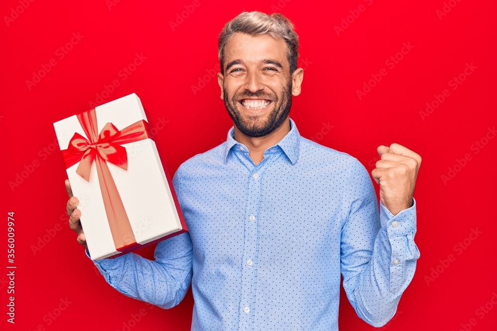 Fototapeta Young handsome blond man with beard holding birthday present over isolated red background screaming proud, celebrating victory and success very excited with raised arm