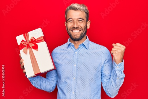 Fototapeta Young handsome blond man with beard holding birthday present over isolated red background screaming proud, celebrating victory and success very excited with raised arm obraz