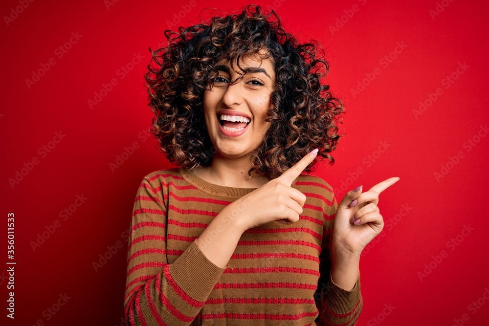Leinwandbild Motiv - Krakenimages.com : Young beautiful curly arab woman wearing casual striped sweater standing over red background smiling and looking at the camera pointing with two hands and fingers to the side.